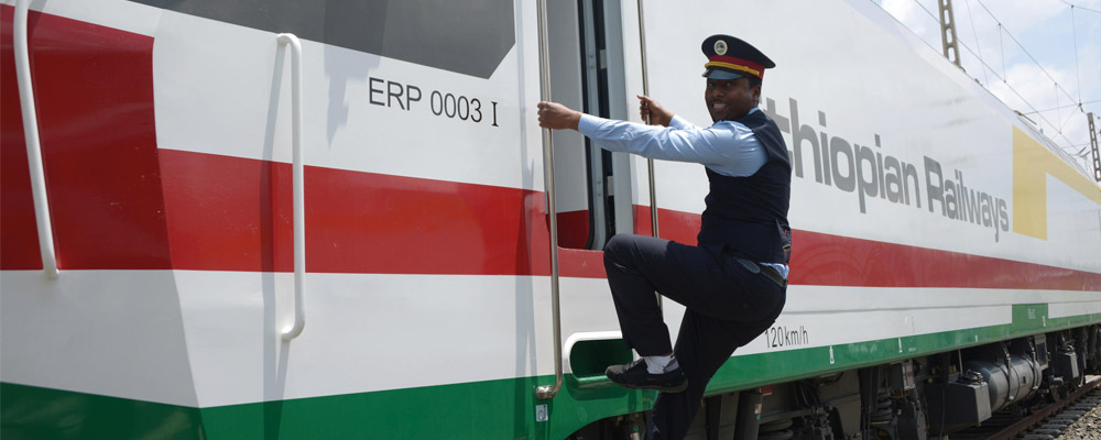 Conductor climbing onto Ethiopian Railways train - Rathbone Investment Management