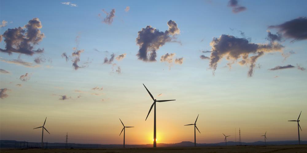 Sunrise behind wind turbines - Rathbone Investment Management