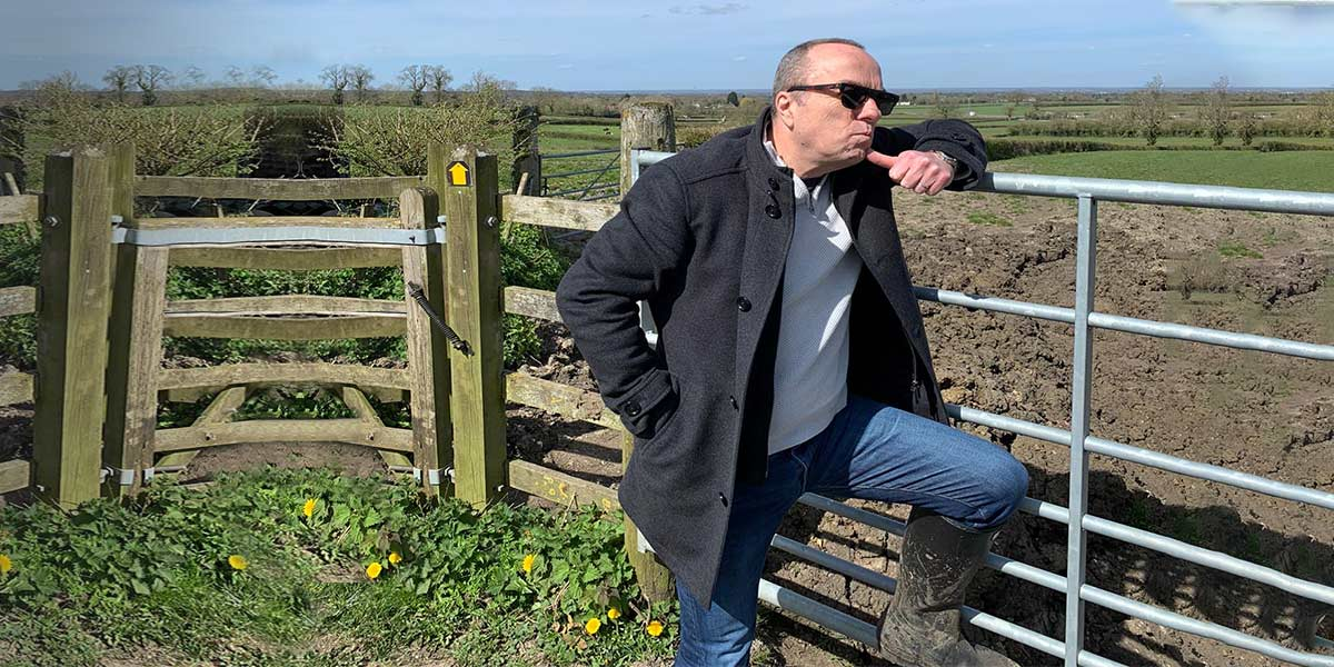 David Coombs fund manager against a fence on a field