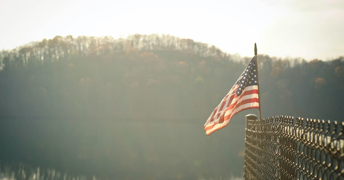 US flag against a lake background