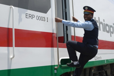 Conductor climbing onto Ethiopian Railways train - Rathbone Investment Management