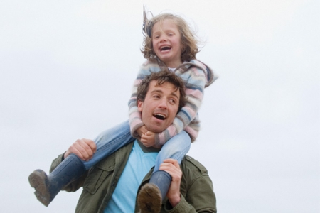 Young girl sat on her fathers shoulders - Rathbone Investment Management