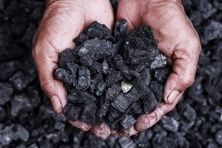 Hands holding coal and a diamond