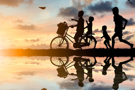 Kids silhouettes with bicycles with a sunset background