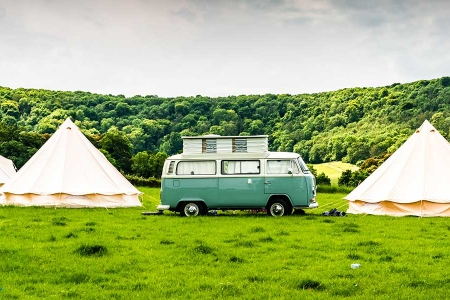 Campervan parked between three tents | Rathbone Investment Management