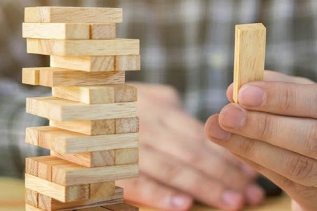 Man playing Jenga with multiple pieces missing