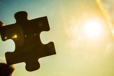 Hand holding jigsaw piece in the sunlight