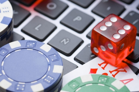 A die, playing card, gambling chips and a keyboard